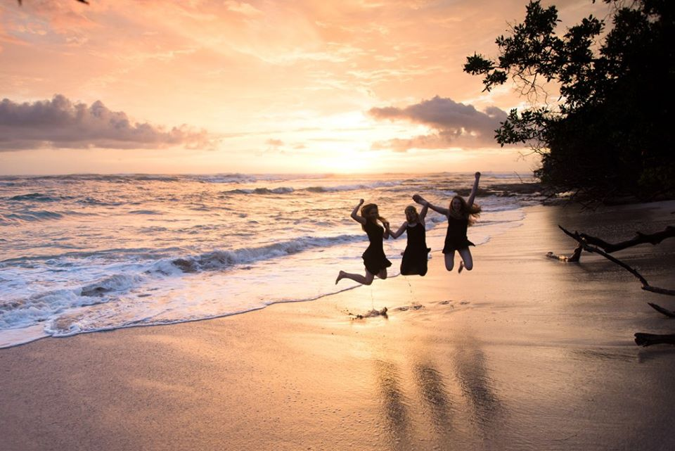 Cousins jumping on the beach during a beautiful sunset in Costa Rica. Photographed by Kristen M. Brown, Samba to the Sea Photography.