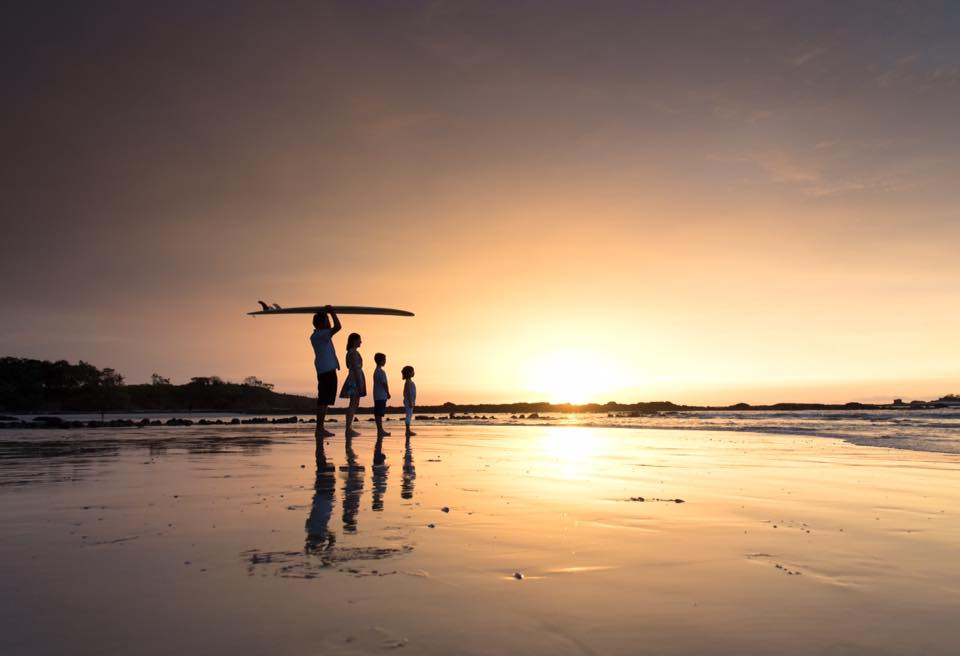Surfer silhouette on the low tide sand in Tamarindo, Costa Rica. Photographed by Samba to the Sea.