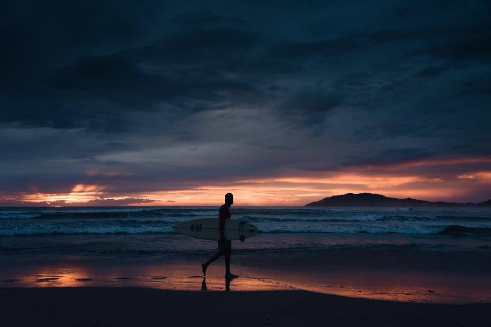Surfer silhouette at sunset in Tamarindo, Costa Rica. hotographed by Samba to the Sea.