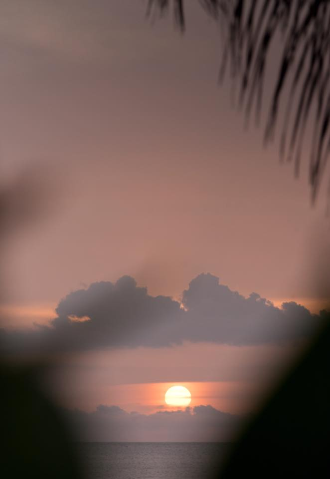 Sun peeking through the clouds during sunset in Tamarindo, Costa Rica. Photographed by Kristen M. Brown, Samba to the Sea Photography.