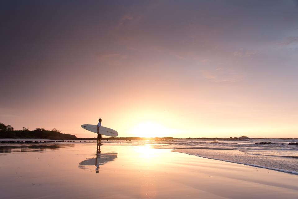 Surfer at sunset in Tamarindo, Costa Rica. Photographed by Samba to the Sea.