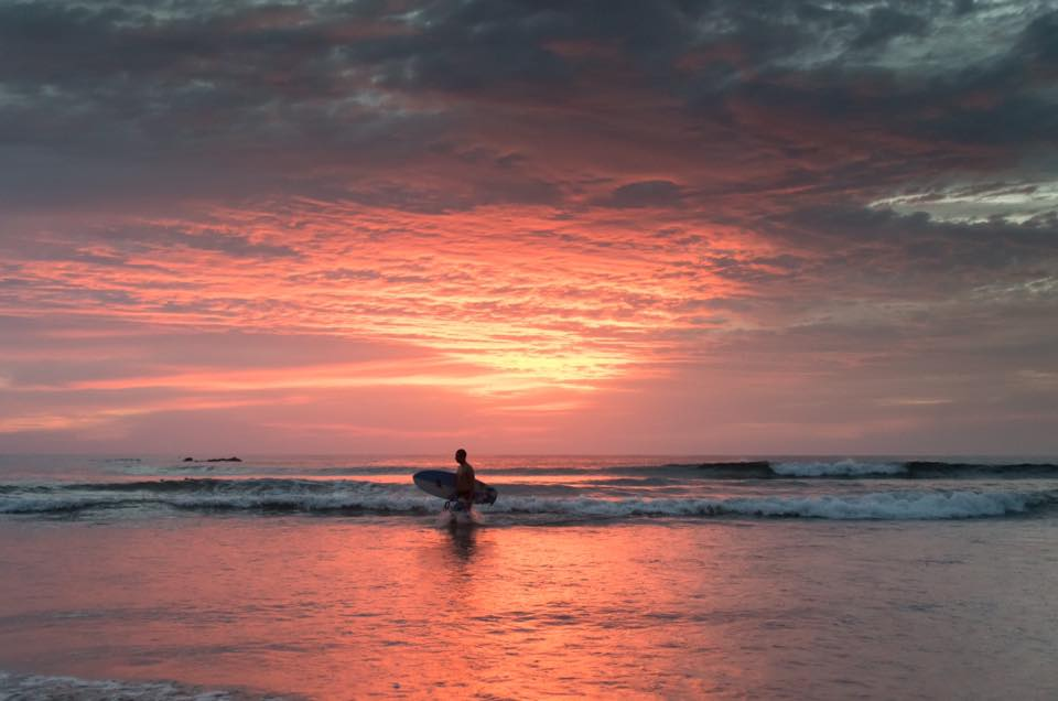 Surfer leaving the ocean during a fire orange sunset in Tamarindo, Costa Rica. Photographed by Kristen M. Brown, Samba to the Sea.