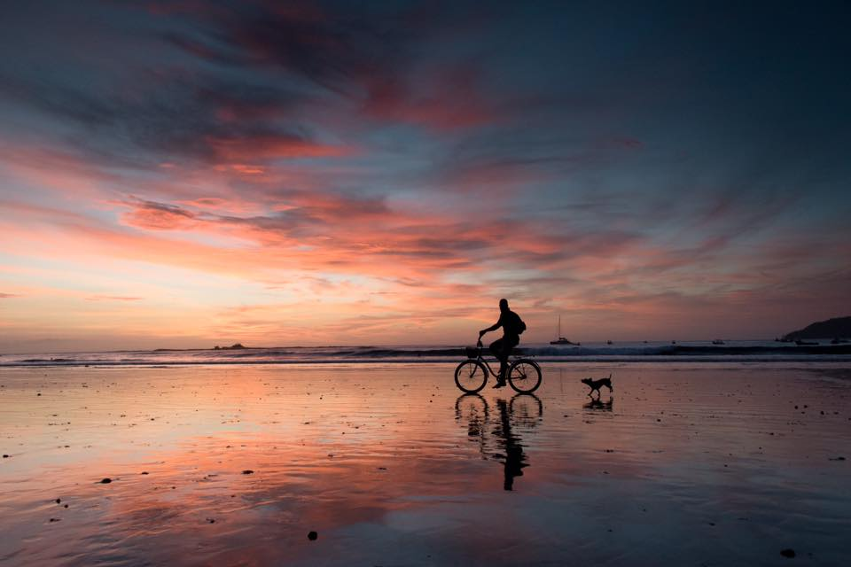 Silhouette on the low tide wet sand of a dog following a man on his bike during a stunning sunset in Tamarindo, Costa Rica. Photographed by Samba to the Sea Photography.
