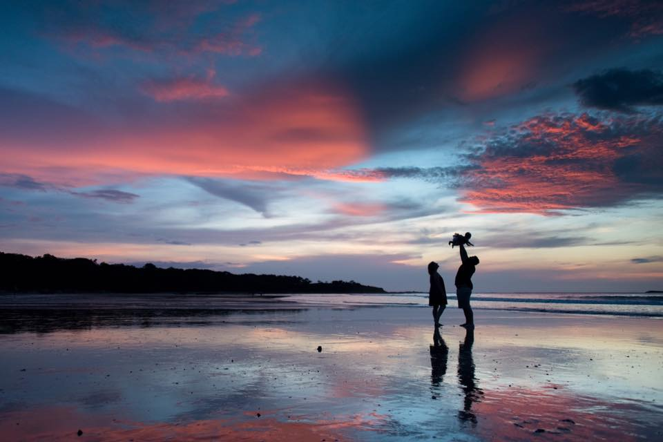 Silhouette of a family on the low tide wet sand during a gorgeous sunset in Costa Rica. Photographed by Samba to the Sea Photography.