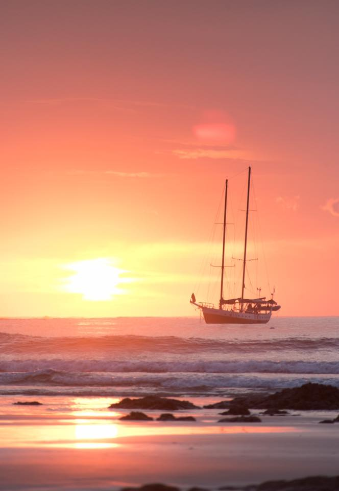 Schooner sailboat and a gorgeous sunset in Costa Rica. Photographed by Samba to the Sea Photography.